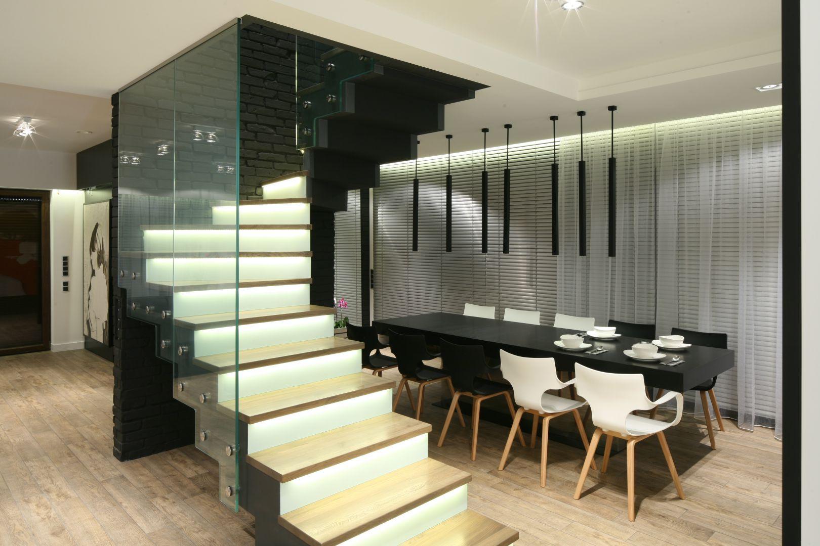 Jadalnię zlokalizowano w bezpośrednim sąsiedztwie otwartych na strefę dzienną schodów. Kolorystycznie stopnie schodów komponują się z krzesłami w jadalni. Fot. Bartosz Jarosz.
