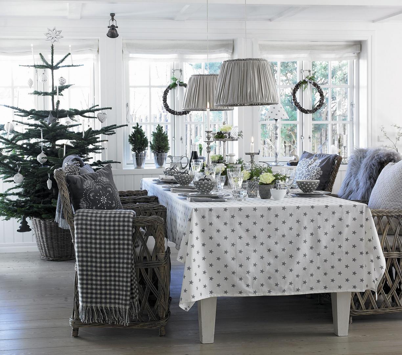 Szaro-biała aranżacja jest niezwykle szykowna. Poduszki ze świątecznymi motywami oraz obrus i zastawa w gwiazdki nadają wnętrzu wyjątkowej przytulności. Fot. Green Gate.
