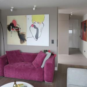 W niewielkim salonie, urządzony w kobiecym stylu, dominują dwie barwy. Zgrabna sofa w kolorze fuksji idealnie prezentuje się na tle szarych ścian. Projekt: Małgorzata Borzyszkowska. Fot. Bartosz Jarosz.