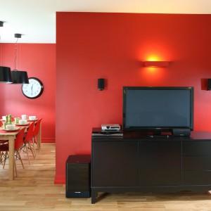 Ścianę z telewizorem, podobnie jak ściany w jadalni, zdominowała czerwień. Ta energetyczna barwa pozwoliła ożywić przestrzeń salonu. Projekt: Dorota Szafrańska. Fot. Bartosz Jarosz.