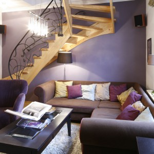W urządzony w klasycznym stylu salonie dominują brązy oraz fiolety. Te ostatnie zdobią też ścianę, na której tle pięknie eksponują się schody. Projekt: Iwona Zasławska. Fot. Bartosz Jarosz.