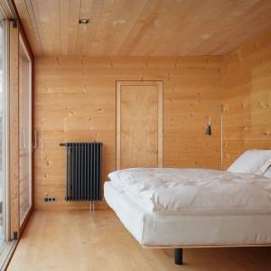 Wnętrze zimowej rezydencji  urządzone w minimalistyczny sposób. Ciekawy rysunek oraz barwa drewna wprowadza do wnętrza przytulną atmosferę. Projekt: Peter Zumthor. Fot. Zumthor Ferienhäuse.