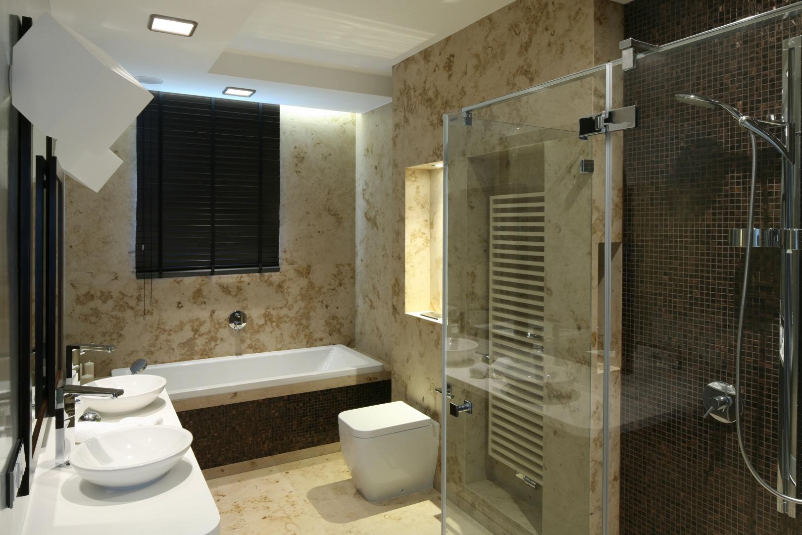 Płytkami kamiennymi wykończono niemal całą łazienkę. Beżowy kamień z charakterystycznym, dekoracyjnym wzorem pięknie koresponduje z brązową mozaika, która akcentuje strefy kąpielowe. Projekt: Katarzyna Koszałka. Fot. Bartosz Jarosz.
