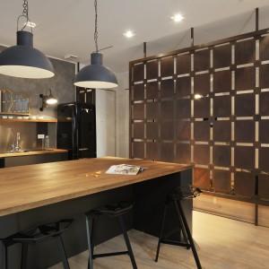 Strefę otwartą od przedpokoju oddziela przepierze wykonane z kortenu. Geometryczny motyw i stalowy materiał idealnie komponują się z loftowymi elementami aranżacji, jak industrialne lampy nad blatem i szara ściana, przywodząca na myśl beton. Projekt: Biuro Architektoniczne GAO Arhitekti. Fot. Miran Kambic.