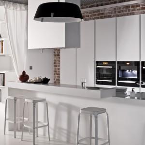 Biała zabudowa kuchenna pięknie kontrastuje z zabudowanym w niej sprzętem AGD. Razem tworzą one efektowną aranżację, czyniąc ze sprzętów, które zostały częściowo schowane, estetyczny element dekoracyjny. Z bielą gładkich frontów zabudowy, harmonizuje biała wyspa oraz ustawione przy niej - również białe - stołki. Fot. ZAJC kuchnie.