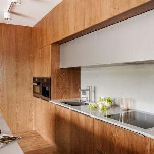Fronty dolnych szafek i zabudowy  pokryto eleganckim dębowym fornirem. Bezpośrednio nad blatem kuchennym zamontowano wiszące szafki, które utrzymano w białym kolorze i polakierowano. Kontrastują one efektownie z otaczającym je ciepłym kolorem dębowego drewna. Całość utrzymano w minimalistycznym stylu, z prostymi liniami, gładkimi, niefrezowanymi powierzchniami i dyskretnymi uchwytami. Fot. ZAJC kuchnie, model Z5.