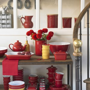 Czerwona zastawa już sama w sobie stanowi mocno dekoracyjny element. Można do niej dobrać kilka subtelnych, spokojnych dodatków. Fot. Emile Henry, kolekcja Classiques.