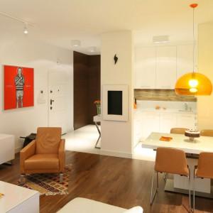 Jadalnia harmonizuje zarówno z kuchnią, jaki i salonem. Stół pasuje do zabudowy, natomiast krzesła do wygodnego fotela. Jadalnię wyeksponowano również przy pomocy lampy w apetycznym, pomarańczowym kolorze. Projekt: Małgorzata Galewska. Fot. Bartosz Jarosz.