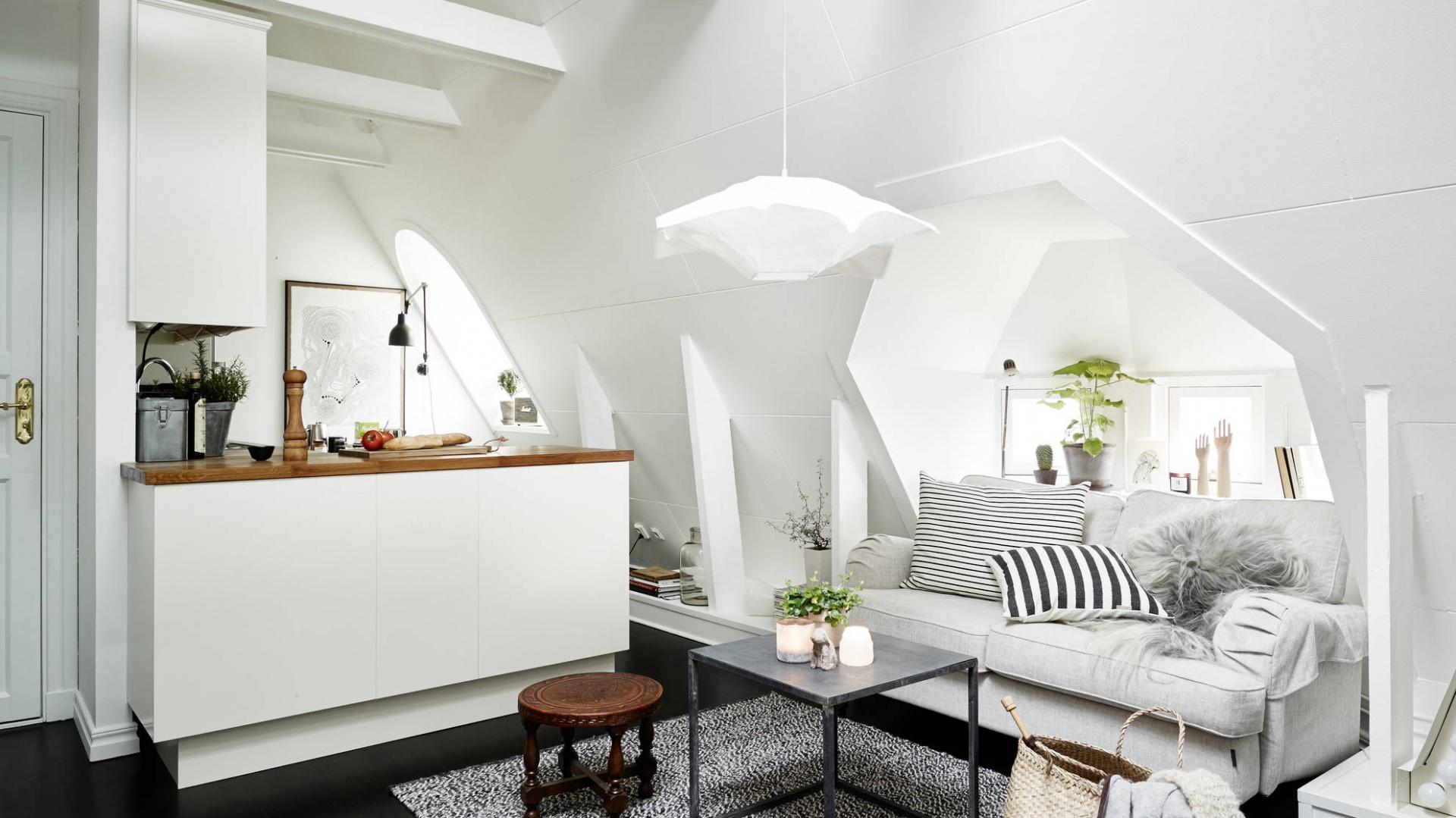Sofę z przytulnymi, dekoracyjnymi tekstyliami wpasowano we wnękę okienną o oryginalnym kształcie. Przed sofą położono miękki, szary dywan, niewielki stołek oraz elegancki stolik kawowy. Całość tworzy przestrzeń salonu. Fot. Stadshem.