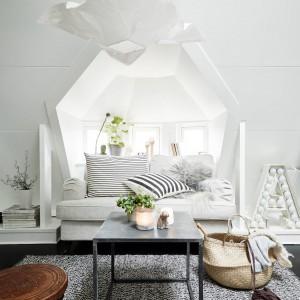 Nad strefą wypoczynkową zawisła oryginalna lampa, która formą i kolorem koresponduje z nietuzinkowym kształtem wnęki okiennej za kanapą. Fot. Stadshem.