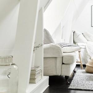 Niewielki podest na styku podłogi ze skośną ścianą, wykorzystano jako podręczną, długą półkę. Można przechowywać tutaj książki i akcesoria dekoracyjne. Poszczególne półki oddzielają belki stropowe, tworząc razem z podestem, jedyny w swoim rodzaju regał. Fot. Stadshem.