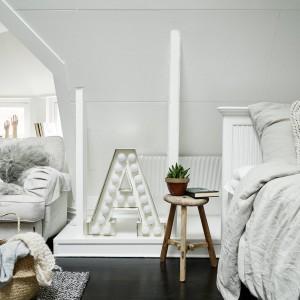 Umowną granicę pomiędzy sypialnią a salonem wydzielają: pełniący rolę kwietnika, stołek z surowego drewna, belki stropowe pod ścianą oraz oryginalna dekoracja z motywem litery A. Fot. Stadshem.