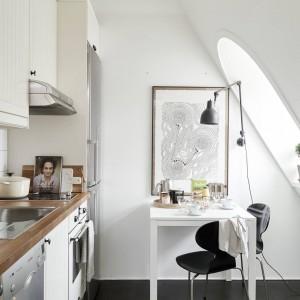 W kuchni znalazło się miejsce na ustawienie niewielkiego stolika, który może pełnić dwojaką funkcję: jadalni oraz niewielkiego gabinetu. Wpadające do środka słońce przez okno w połaci dachu, rozświetla powierzchnię stołu. Fot. Stadshem.