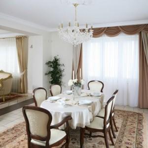 Złoto i biel to połączenie subtelności i przepychu - idealne na świąteczną kolację. Odświętną atmosferę tworzą dekoracyjne świeczniki, złote pasy na bieżnikach, a także... komponujący się kolorystycznie z nakryciem stołu, dekoracyjny żyrandol. Projekt wnętrza: Małgorzata Goś. Fot. Bartosz Jarosz.