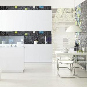 Białe meble kuchenne i podłoga zostały przełamane przez kolorową mozaikę na ścianach. Ciemne powierzchnie estetycznie eksponują białe meble, dodając całej aranżacji lekko popartowego, ale i eleganckiego charakteru. Fot. Ceramika Paradyż.