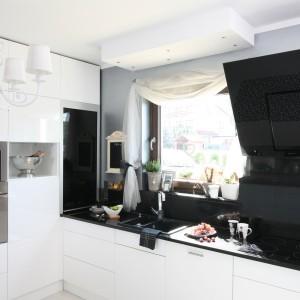 Elegancka czarno-biała kuchnia, w której styl glamour zaznaczono poprzez połyskujące powierzchnie blatu i ściany nad nim oraz ozdobny, biały żyrandol. Projekt: Magdalena Konochowicz. Fot. Bartosz Jarosz.