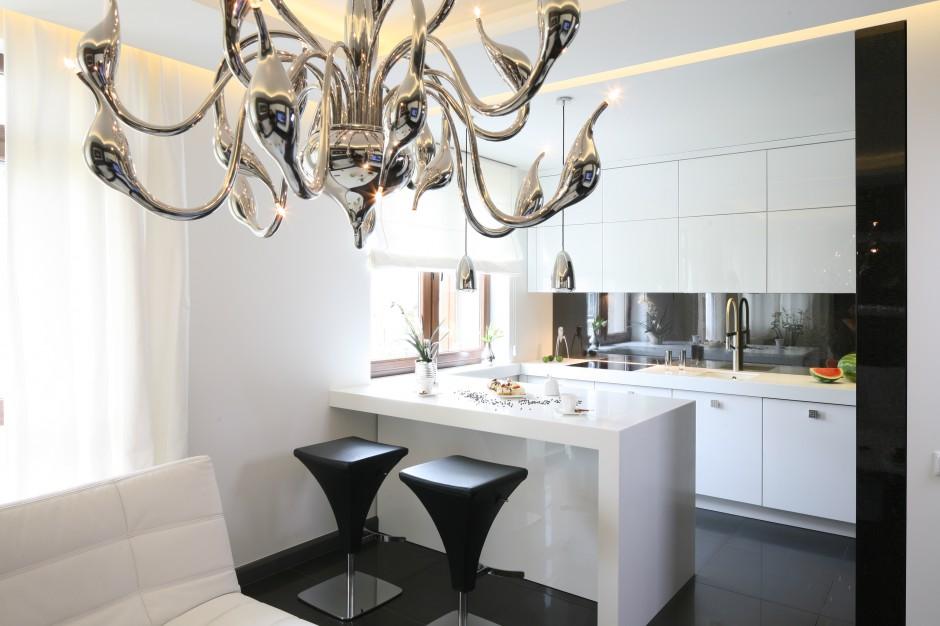W eleganckiej czarno-białej kuchni elementem dekoracyjnym, przyciągającym wzrok jest piękny żyrandol, którego poszczególne ramiona przechodzą w stylowe, srebrne łabędzie głowy. Projekt: Łukasz Sałek. Fot. Bartosz Jarosz.