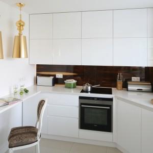 Piękna biała kuchnia, w której nowoczesne fronty mebli kuchennych bez uchwytów, skomponowano ze stylizowanymi akcentami. Są nimi zdobione krzesło z wzorzystą tapicerką i pozłacane, stylizowane lampy. Projekt: Katarzyna Merta-Korzniakow. Fot. Bartosz Jarosz.