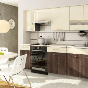 Biały stół i krzesła, skomponowano z kremowymi frontami górnych szafek i szuflad pod blatem kuchennym. Powierzchnię nad blatem pozostawiono w uniwersalnej bieli, komponującej się z biała podłogą. Mocniejszym akcentem są fronty dolnych szafek - wykończone ciemnym, czekoladowym brązem z drewnianym dekorem. Fot. Stolkar, kuchnia Luxe Magnolia.