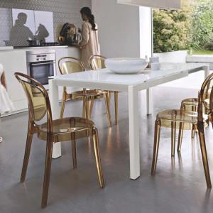 Biały, nowoczesny stół pięknie kontrastuje się z szarością podłogi i powierzchni nad blatem. Aranżację uzupełniają białe meble kuchenne o nowoczesnej formie i przeźroczyste krzesła o ciepłym, miodowym wybarwieniu. Fot. Kler, model stołu Parisienne.