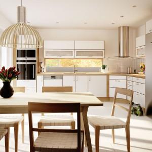 Białe meble kuchenne, ocielone jasnym drewnem zestawiono z jasnobrązowym stołem i krzesłami w jadalni. Nad powierzchnią roboczą - delikatny akcent w jasnym odcieniu szarości. Rozświetlona przestrzeń pomieszczenia napawa optymizmem i dodaje energii. Fot. Ballingslov, linia Style.