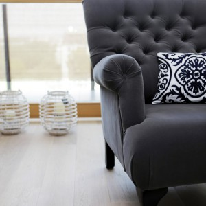 Meble wypoczynkowe w salonie pełnią także rolę stylowej dekoracji. Piękne zdobione nogi i tapicerowane oparcie nadają pomieszczeniu eleganckiego szyku. W tle dekoracyjne latarenki. Projekt: Chalupko Design. Fot. Chalupko Design.
