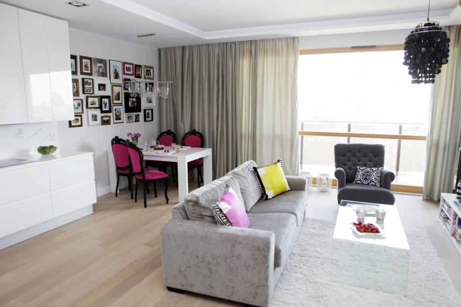 Podłogę w otwartej strefie salonu i kuchni wykończono drewnianą podłogą z bielonego dębu. Jednorodna posadzka spaja wizualnie oba pomieszczenia i optycznie je powiększa. Jasny brąz ociepla subtelnie chłodną aranżację, zdominowaną przez szarości i biel. Odważnym akcentem dekoracyjnym są barwne poduszki i intensywnie różowe tapicerki krzeseł w kąciku jadalnianym. Projekt: Chalupko Design. Fot. Chalupko Design.
