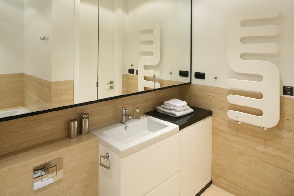 Na całej szerokości ściany, nad umywalką oraz sanitariatami zamontowano wiszące szafki z lustrzanymi frontami. Taki mebel nie tylko pomieści wszystkie niezbędne akcesoria, ale także optycznie powiększy przestrzeń. Projekt: Anna Maria Sokołowska. Fot. Bartosz Jarosz.