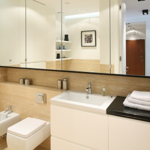 Lustrzane fronty szafek sięgają do samego sufitu, dlatego odbija się w nich niemal cała łazienka. Daje to wrażenie głębi i znacznie powiększa wizualną przestrzeń. Projekt: Anna Maria Sokołowska. Fot. Bartosz Jarosz.
