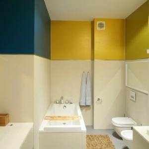 Nie tylko lustra, których w tej łazience jest aż trzy ale także  kolorowy fragmenty ścian, których pas wyraźnie odcina się od całości powodują, że łazienka wydaje się większa i wyższa. Projekt: Konrad Grodziński. Fot. Bartosz Jarosz.