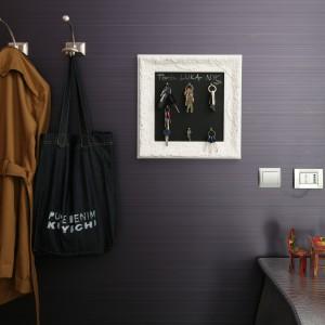 W przedpokoju zadbano o każdy detal - eleganckie w formie wieszaczki na ubrania oraz półka na klucze idealnie komponują się na tle fioletowej ściany. Mini mebelki ustawione na komodzie zapraszają na filiżankę kawy lub herbaty. Projekt: Joanna Nawrocka. Fot. Bartosz Jarosz.