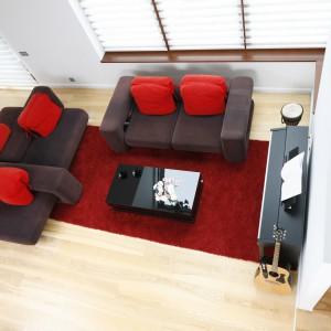 Z dywanem w salonie kolorystycznie komponują się dekoracyjne poduszki, zdobiące meble wypoczynkowe. Poprowadzony od ściany do ściany dywan, przeistacza się w pas kolorowej zabudowy. Projekt: Michał Mikołajczak. Fot. Bartosz Jarosz.