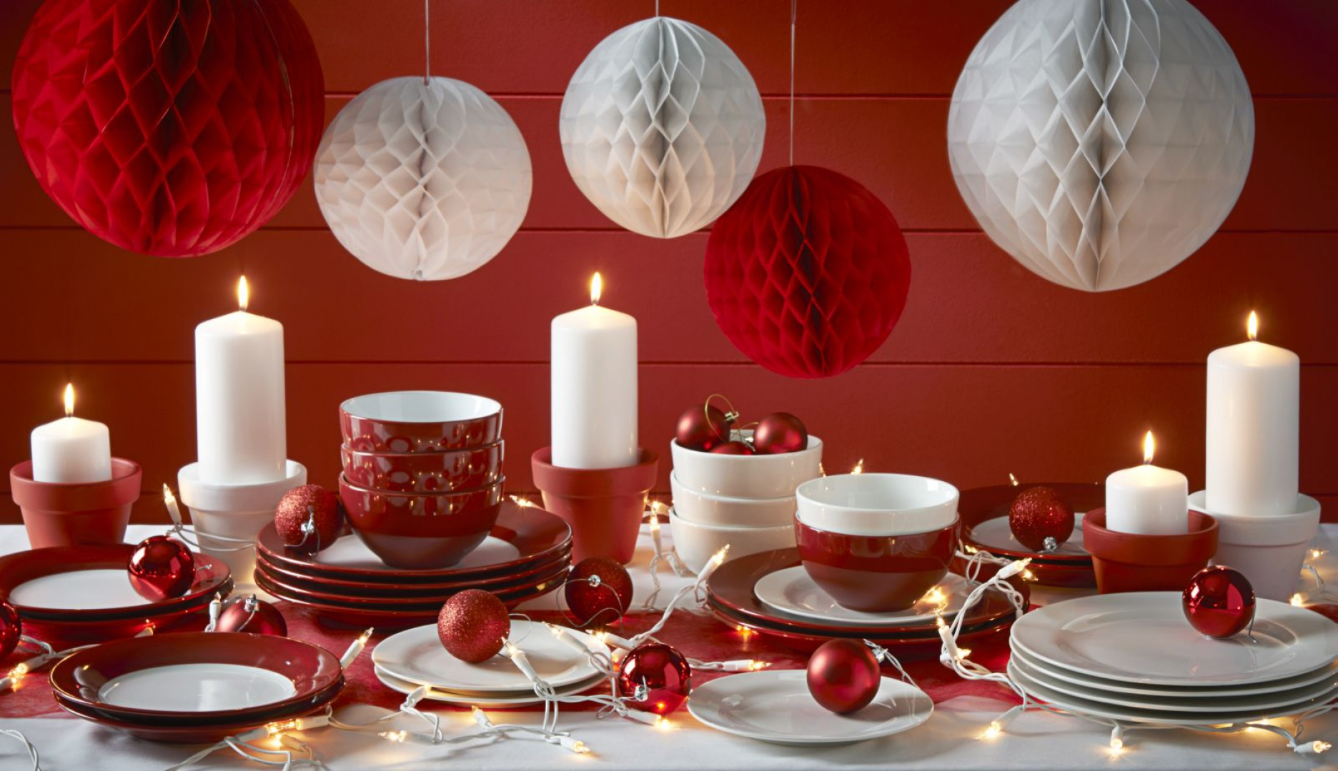 Świąteczną aranżację w czerwieni możemy stworzyć bazując na przedmiotach, które mamy w domu. Wystarczy, że do białe świece wstawimy w czerwony świecznik a do białych talerzy dokupimy czerwone bulionówki i serwetki. Fot. Wilko.