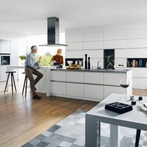 Nowoczesna kuchnia z dużą, długą, szeroką wyspą i wysoką zabudową kuchenną. Wszystkie funkcje robocze zostały przeniesione na wyspę, w obrębie której znajdziemy zlewozmywak, długi blat kuchenny, powierzchnie do gotowania oraz całkiem spory barek. Zlokalizowany na podniesionym, wysuniętym blacie pozwala na komfortowy relaks, a bliskie sąsiedztwo z płytą grzewczą, umożliwia swobodną interakcję z osobą, przygotowującą posiłek. Fot. Schueller, kolekcja Glasline.