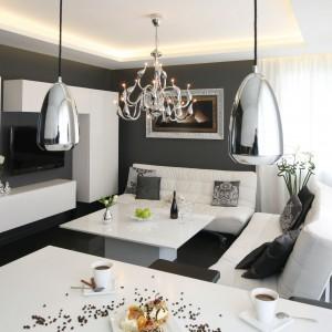 Czarno-biały salon urządzono w stylu glamour. Konwencję stylistyczną wnętrza podkreślają lakierowane na wysoki połysk powierzchnie białych mebli, w tym szafki RTV, a przede wszystkim srebrne oświetlenie. Projekt: Łukasz Sałek. Fot. Bartosz Jarosz.