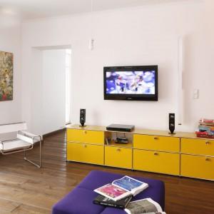 W stylowym wnętrzu spotykają się nowoczesność i tradycja. Stąd do ceglanych ścian dobrano żółtą szafkę RTV. Projekt: Konrad Grodziński. Fot. Bartosz Jarosz.