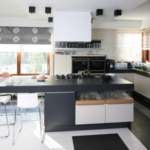 Otwarta kuchnia stanowi prawdziwe centrum gotowania. Zaplanowany aż na cztery osoby barek śniadaniowy stanowi przedłużenie obszernej wyspy ze zintegrowaną strefą gotowania. Projekt Małgorzata Borzyszkowska. Fot. Bartosz Jarosz.