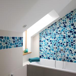 Ściana nad wanna, której kształt wyznacza skos dachowy została wykończona mozaika w odcieniach   błękitu. Projekt: Małgorzata Galewska. Fot. Bartosz Jarosz.