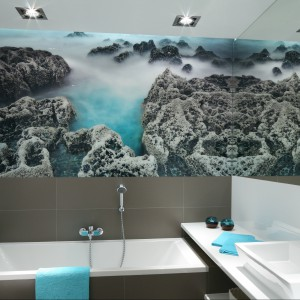W tej pomysłowej łazience dla rodziny ściana nad wanną została wykończona fototapetą z motywem rafy koralowej. Lustro na sąsiedniej ścianie dodatkowo wzmacnia efekt. Projekt: Anna Maria  Sokołowska. Fot. Bartosz Jarosz.