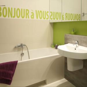 W kolorowej łazience dla rodziny do wykończenia ściany nad wanną wykorzystano płytki ceramiczne oraz farbę. Za pomocą specjalnego szablonu wykonano nad wanną oryginalny napis zapraszający do kąpieli. Projekt: Marta Kruk. Fot. Bartosz Jarosz.