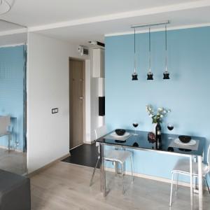 Przestrzeń jadalni zaznacza pomalowana błękitem ściana, pełniąca rolę ścianki działowej pomiędzy kuchnią a przestrzenią salonu. Na jednej ze ścian ułożono lustrzaną mozaikę, która pełni nie tylko rolę efektownej dekoracji, ale także znacznie powiększa optycznie wnętrze. Projekt: Marta i Tomasz Kilan. Fot. Bartosz Jarosz.