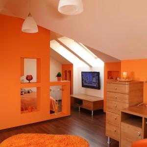 Większość wyposażenia stanowią meble w kolorze jasnego drewna. Wyjątkiem jest sofa i designerski fotel obrotowy. Fot. Bartosz Jarosz.