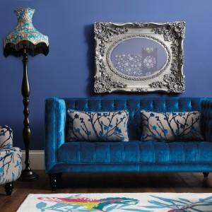 Wyrafinowany zestaw mebli marki Very tworzy pikowana sofa oraz puf wyściełane połyskującym atłasem, a także fotel ozdobiony motywem roślinnym. Fot. Very.