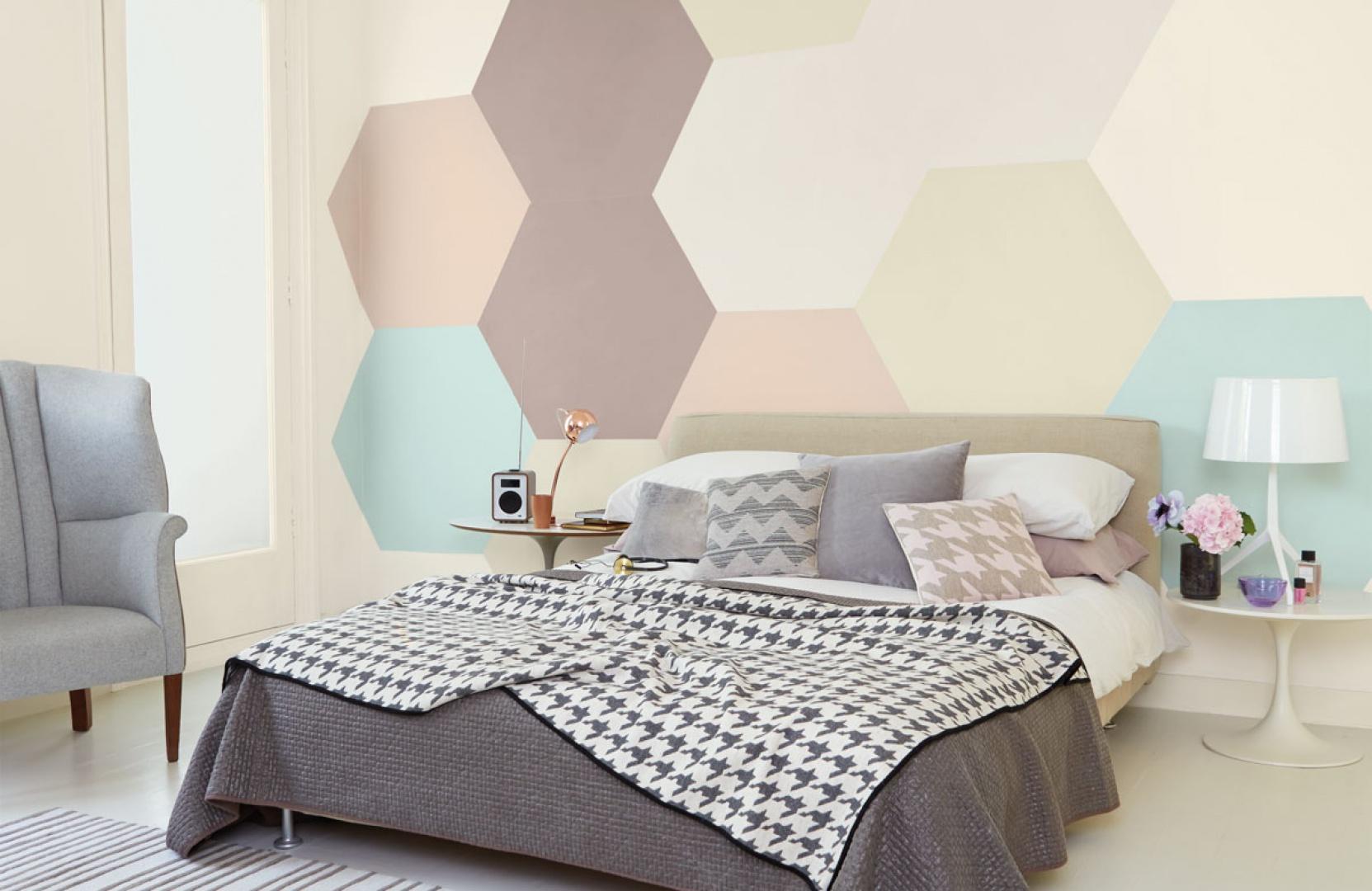 Pastelowe sześciokąty: delikatne beże, brązy, szarości i błękity tworzą na ścianie za łóżkiem oryginalną dekorację. Fot. Dulux.
