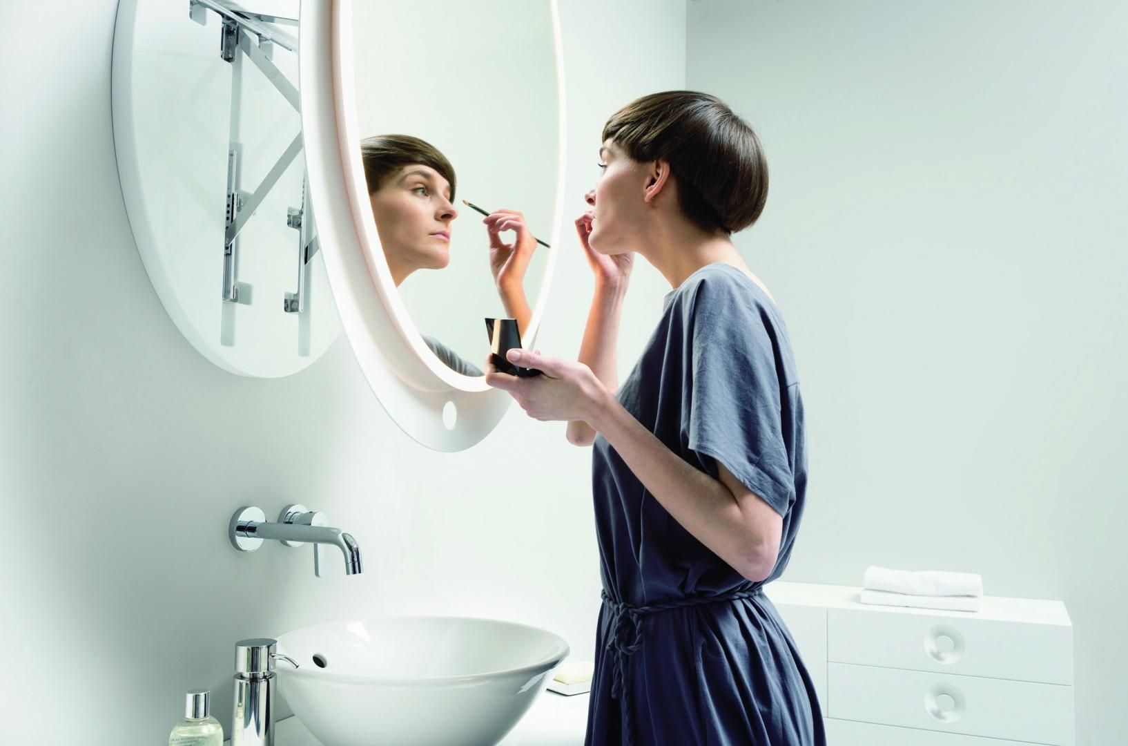 Lustro Ella firmy Miior ma delikatny i kobiecy, a jednocześnie nowoczesny styl, owalne (93x63 cm); technologia Axio-Link umożliwia dopasować dystans pomiędzy twarzą a lustrem bez przyjmowania niewygodnej pozycji podczas codziennej toalety – wystarczy pociągnąć za ramę; czujnik ruchu pod powierzchnią lustra włącza oświetlenie. Fot. Miior.
