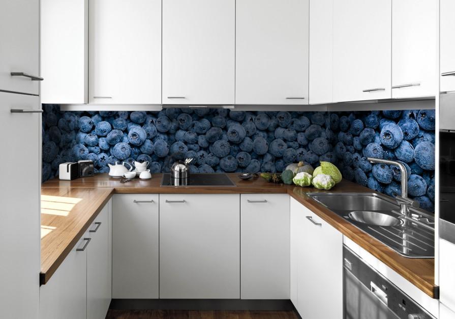 Jagody w intensywnym kolorze granatu to ciekawy sposób na mocniejszy akcent kolorystyczny w białej kuchni, ocieplonej drewnem. Kontrastująca z meblami kuchennymi ściana, prezentuje się elegancko i... zachęca do wycieczki do lasu. Fot. Picassi.