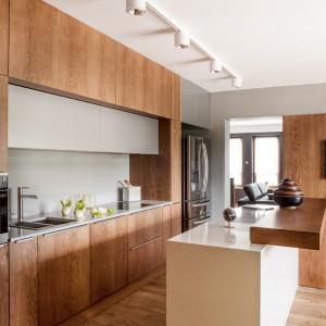 Piękna kuchnia, w której nowoczesną formę zestawiono z bogato użytymi akcentami drewnianymi. Fronty mebli w naturalnej okleinie nadają przestrzeni ciepłego, domowego klimatu. Idealnie komponują się z podłogą i beżową wyspą wykonaną z konglomeratu. Fot. ZAJC kuchnie, model Z5/kuchnia 028.