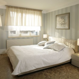 Ciekawa aranżacja okna, spójnie dobrane oświetlenie i łagodna kolorystyka tworzą elegancką, klasyczną sypialnię. Projekt: Małgorzata Borzyszkowska. Fot. Bartosz Jarosz.