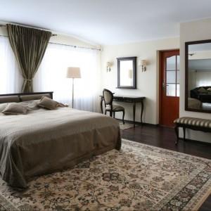 Centralnym elementem w przestronnej sypialni jest łóżko. Klasyczna forma współgra z pozostałymi, stylowymi meblami: toaletką, stolikami nocnymi. Projekt: Małgorzata Goś. Fot. Bartosz Jarosz.