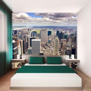 Kolorowa fototapeta z widokiem na wieżowce zdominowała wnętrze sypialni. Meble w minimalistycznej formie doskonale pasują do widoku umieszczonego na ścianie.  Fot. Artasaż.